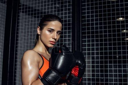 Photo pour Boxeur sportif dans des gants de boxe restant près de filet de fil et regardant l'appareil-photo - image libre de droit