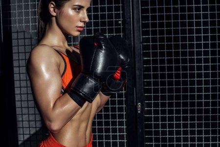 Photo pour Boxer sportif en gants de boxe debout près d'un filet métallique et regardant ailleurs - image libre de droit