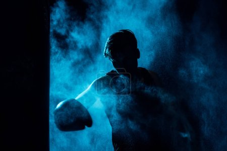 Photo for Boxer in boxing gloves training in dark with smoke - Royalty Free Image