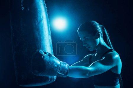 Photo pour Boxeur féminin confiant avec l'entraînement de queue de cheval avec le sac de poinçonnage - image libre de droit