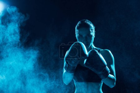 Front view of serious boxer in boxing gloves looking at camera