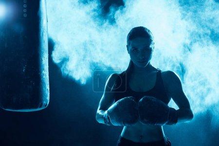 Photo pour Vue de face de boxeur confiant dans des gants de boxe regardant l'appareil-photo - image libre de droit