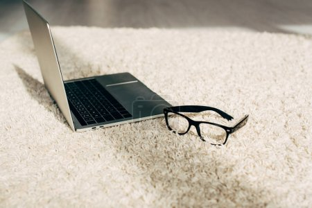 Photo for Modern laptop near glasses on carpet in room with sunshine - Royalty Free Image