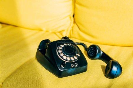 Foto de Sol en el teléfono retro negro en el sofá amarillo - Imagen libre de derechos