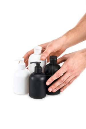 Photo for Partial view of man holding cosmetic bottles on white - Royalty Free Image