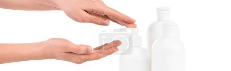 Photo for Panoramic shot of girl with cosmetic bottles applying cream isolated on white - Royalty Free Image