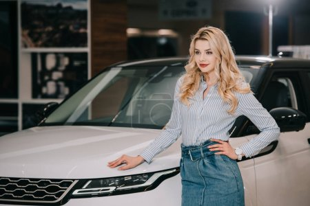 Photo for Happy blonde girl standing with hand on hip near white automobile - Royalty Free Image