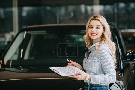 Photo pour Joyeux concessionnaire de voitures blondes tenant presse-papiers avec contrat et stylo - image libre de droit