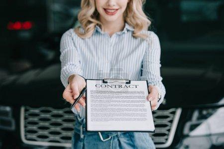 Photo pour Recadrée vue de concessionnaire de voiture heureux tenant le presse-papiers avec contrat et stylo - image libre de droit