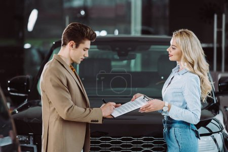 Photo for Handsome man signing contract while standing with happy blonde car dealer - Royalty Free Image