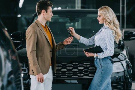 Photo pour Concessionnaire de voiture attrayant donnant la clef à l'homme bel dans le showroom de voiture - image libre de droit
