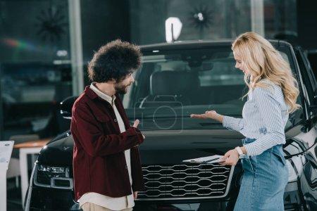 Photo pour Concessionnaire de voiture blonde montrant l'automobile noire à l'homme bouclé - image libre de droit