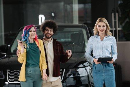 Photo pour Attrayant concessionnaire de voiture blonde tenant le presse-papiers près homme gai et femme - image libre de droit