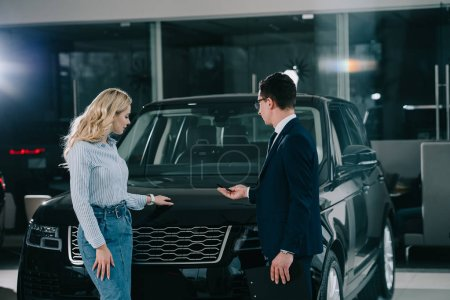 Photo for Car dealer showing automobile to blonde woman in car showroom - Royalty Free Image