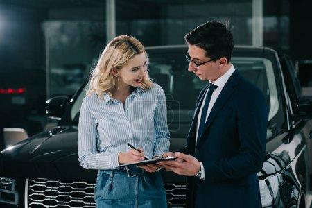 Photo pour Gai femme blonde signant contrat et regardant concessionnaire automobile - image libre de droit