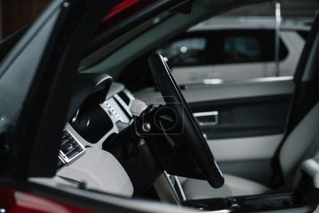 selective focus of black steering wheel in modern automobile