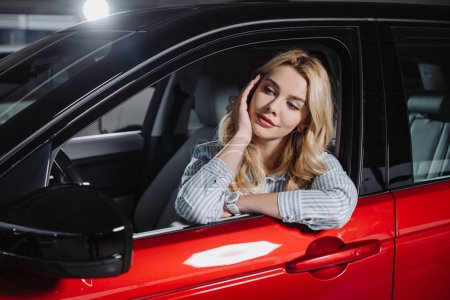 Photo for Beautiful young woman sitting in red automobile in car showroom - Royalty Free Image