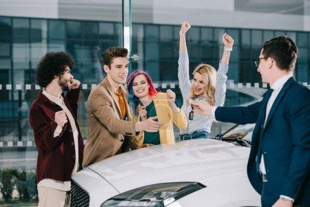 Foto de Concesionario de coches dando la llave a amigos felices de pie cerca de coche blanco - Imagen libre de derechos