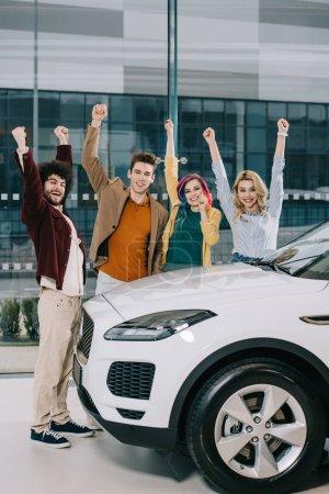 Photo pour Amis joyeux debout avec les mains au-dessus de la tête près de voiture blanche - image libre de droit