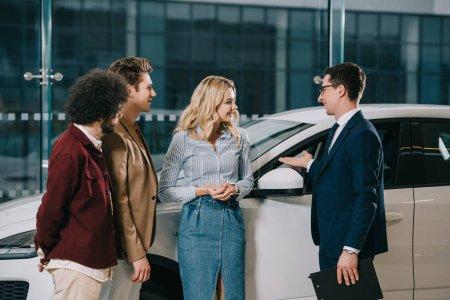 Photo pour Beau concessionnaire de voiture geste tout en se tenant près des amis joyeux dans la salle d'exposition de voiture - image libre de droit