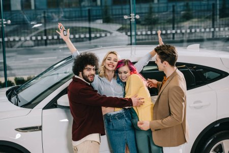 Photo for Cheerful group of friends hugging with attractive blonde girl near white car - Royalty Free Image