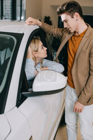 handsome man looking at attractive blonde young woman sitting in car