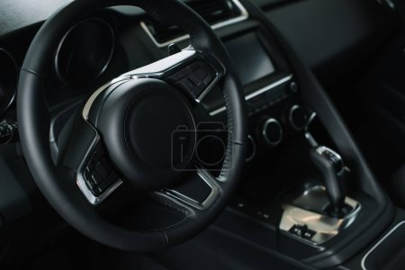 selective focus of steering wheel near gear shift handle in luxury car