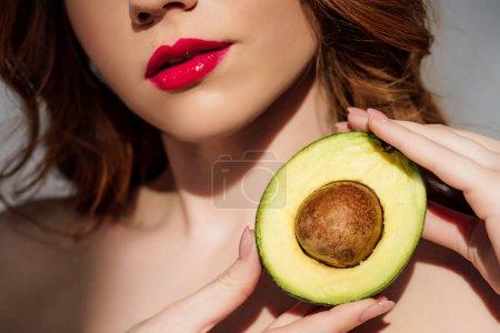 abgeschnittene Ansicht von Mädchen mit roten Lippen posiert mit geschnittener Avocado