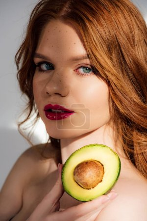 beautiful redhead girl with red lips looking at camera and posing with cut avocado