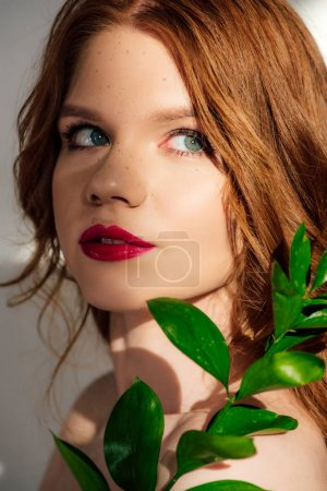 Photo for Beautiful young redhead woman posing with plant and looking away - Royalty Free Image