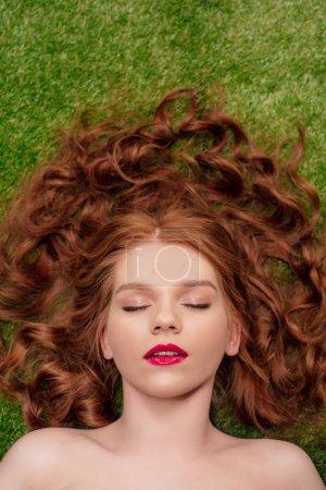 Photo pour Vue de dessus de belle jeune femme rousse avec des lèvres rouges et les yeux fermés - image libre de droit