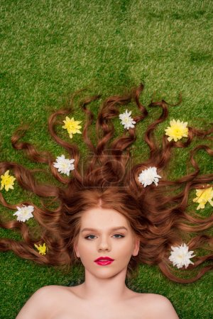 Photo for Top view of beautiful young redhead woman with red lips and chrysanthemum flowers in hair on grass - Royalty Free Image