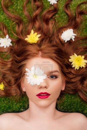 vista superior de la hermosa mujer joven con labios rojos y flores de crisantemo en el pelo en la hierba