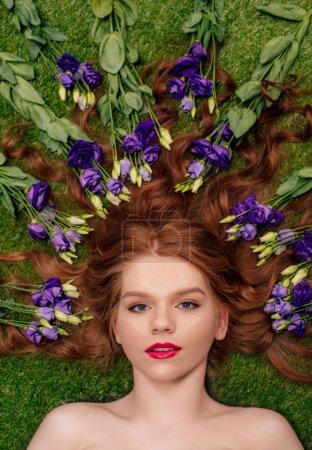 Foto de Vista superior de la hermosa mujer pelirroja joven con los labios rojos y las flores de Eustoma en el pelo - Imagen libre de derechos