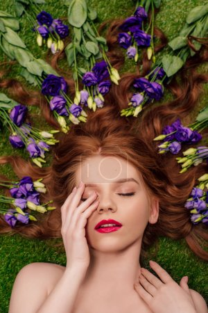 Photo for Top view of beautiful young redhead woman with red lips and eustoma flowers in hair - Royalty Free Image