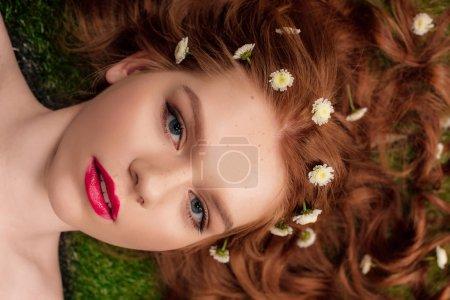 belle jeune femme rousse avec des lèvres rouges et des fleurs de chrysanthème dans les cheveux en regardant la caméra