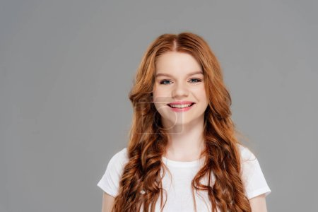 beautiful redhead girl in white t-shirt looking at camera and smiling isolated on grey with copy space