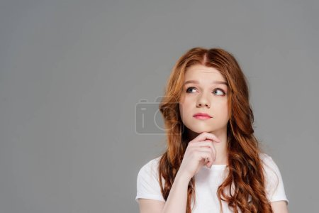 Photo for Thoughtful redhead girl propping chin with hand isolated on grey with copy space - Royalty Free Image