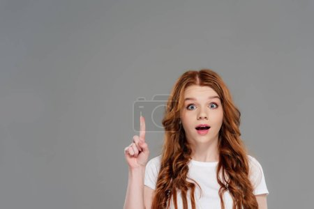 Photo for Beautiful surprised redhead girl looking at camera and showing idea gesture isolated on grey with copy space - Royalty Free Image