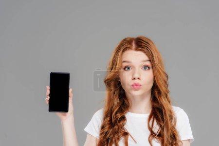 Photo pour Belle fille rousse avec le visage de canard regardant l'appareil-photo et montrant le smartphone avec l'écran blanc isolé sur le gris - image libre de droit