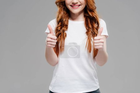 cropped view of smiling redhead girl showing thumbs up isolated on grey