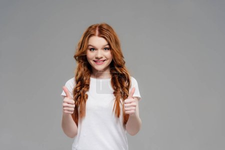 Photo for Beautiful redhead girl looking at camera, smiling and showing thumbs up isolated on grey with copy space - Royalty Free Image