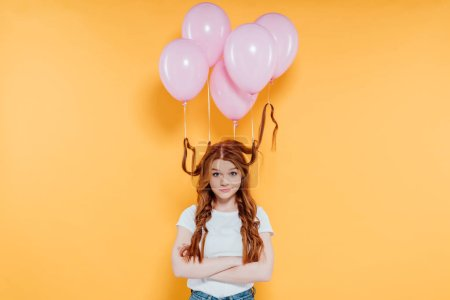 redhead girl with balloons tied to hair looking at camera and posing with crossed arms isolated on yellow