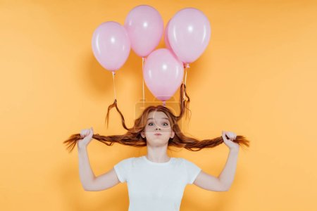 redhead girl with balloons tied to hair blowing cheeks and looking at camera isolated on yellow