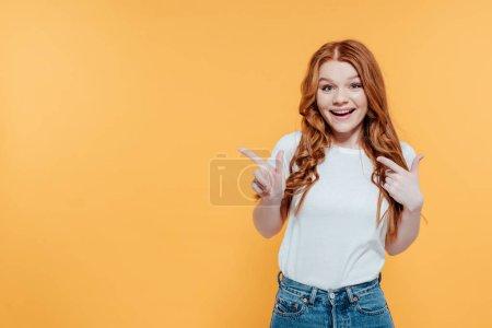 Photo pour Belle fille rousse souriante regardant la caméra et pointant avec les doigts isolés sur jaune avec espace de copie - image libre de droit