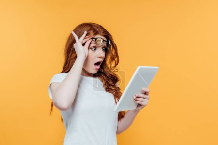 Photo for Surprised redhead girl with glasses using digital tablet isolated on yellow - Royalty Free Image
