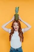 """Постер, картина, фотообои """"веселый рыжий девушка смотрит на камеру и позирует с ананасом на голове изолированы на желтый"""""""