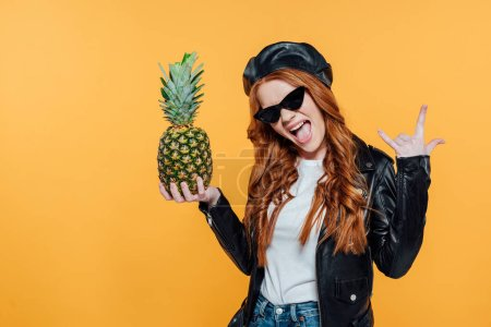 Photo for Redhead girl in leather jacket posing with pineapple and showing rock sign isolated on yellow - Royalty Free Image
