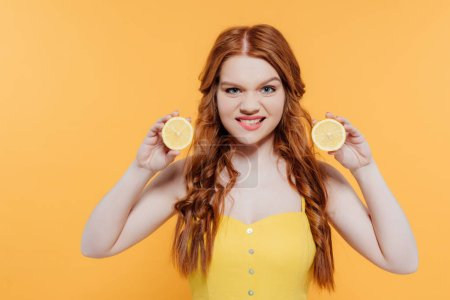 Photo pour Fille rousse retenant des citrons, regardant l'appareil-photo et faisant l'expression faciale d'isolement sur le jaune - image libre de droit