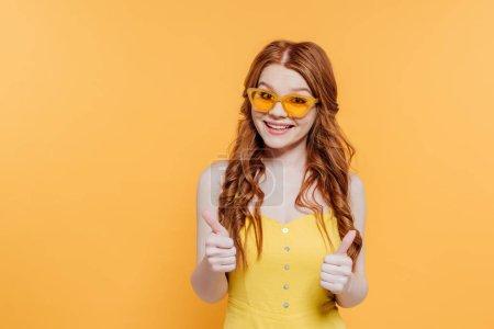Photo pour Belle rousse fille en lunettes de soleil regardant caméra et montrant pouces isolés sur jaune - image libre de droit